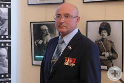Коллекционер и автор выставки В.П.Пестряк-Головатый на фоне фото-экспонатов